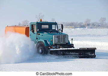Snowplow is cleaning a road and snow flying around it