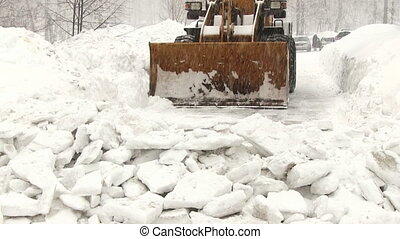 Snowplow removes a lot of snow in the city