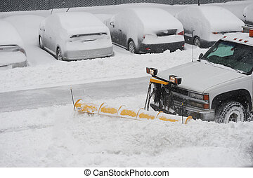 snowplow removing snow on the street after blizzard