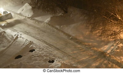 Snowplow truck cleaning the road at night