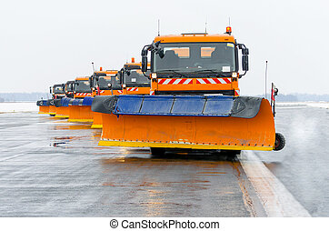 Snowplows in the work on the runway at the airport.