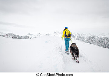 Snowshoeing in the mountains a single woman with her beloved dog