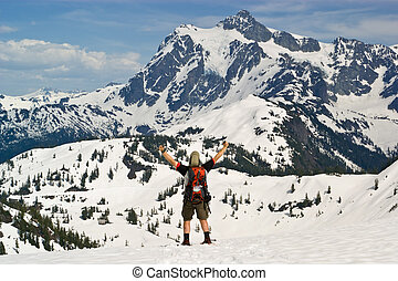 A snowshoer raises his hands in victory at attaining a scenic pass with Mt. Shuksan in Washington State in view.