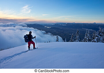 A male snowshoer pauses at a viewpoint to view the scenery below.