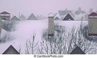 Snowstorm above sloped roofs of residential houses