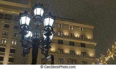 Snowstorm during the New Year holidays. Street lamp shines...
