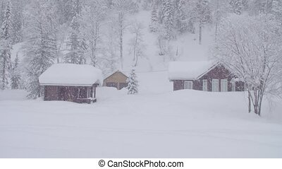 Snowstorm in skitouring lodge in Siberia. Houses covered...