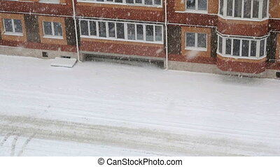 Snowstorm. Multi-storey building on the courtyard -...