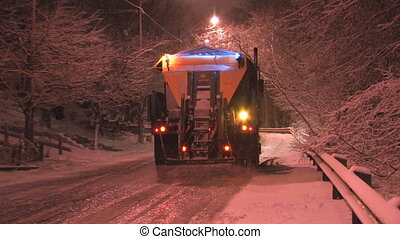 Salt truck driving up a steep hill, laying salt on a snowy, city street. Snowstorm at night in Toronto, Ontario.
