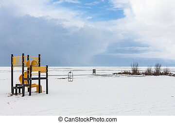Snowy beach near a frozen sea with a playground for children
