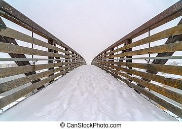 Snowy bridge with footsteps during winter in Utah