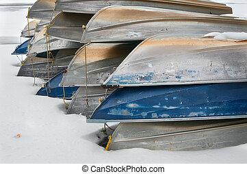 Snowy canoes along a lake shore