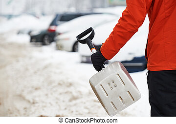 Snowy car cleaning concept. Hand with shovel in winter