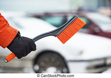 Snowy car cleaning concept. Hand with brush in winter