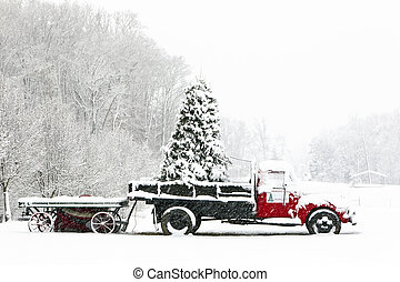 A snow covered truck sits in a field during the Christmas holiday season