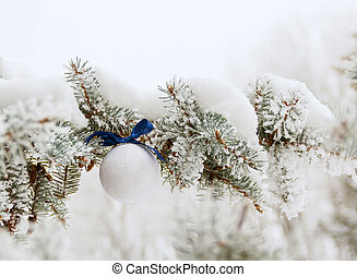 Snowy Christmas pine branch and white ball with blue bow