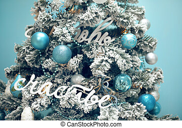 Snowy Christmas tree with blue gifts decoration isolated on turquoise background. December, winter holiday xmas.
