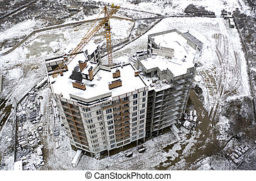 Snowy construction site and crane. Drone view.