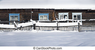 Snowy fence in the countryside. The snow sparkles in the sun. Rural winter scene. HDR - high dynamic range.