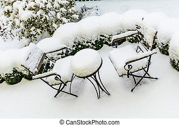 snowy garden furniture, symbolizing winter, winter break, a...