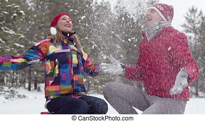 Snowy - Girl and guy enjoying a winter day throwing snow up
