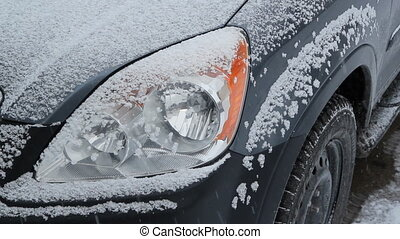 Snowy headlight. - Detail of SUV headlight during snowstorm....