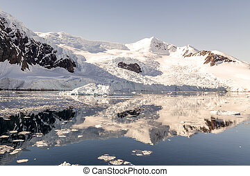 Snowy mountain peak and the glacier reflected in the Antarctic waters of Neco bay, Antarctica