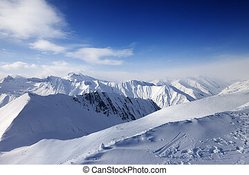 Snowy mountains and blue sky. Caucasus Mountains, Georgia, ski resort Gudauri.
