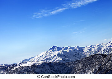 Snowy mountains and blue sky in early sunny morning
