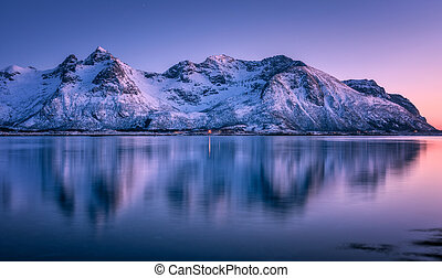 Snowy mountains and colorful sky reflected in water at sunset