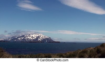 Snowy mountains on background of blue sky with clouds and ocean in Antarctica.