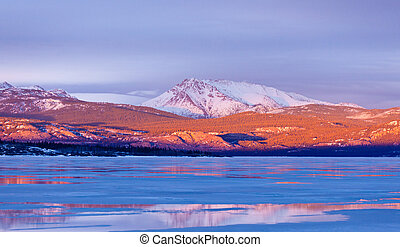 Snowy Mt Laurier frozen Lake Laberge Yukon Canada - Warm...