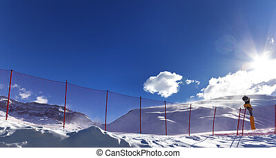 Snowy off-piste ski slope and snow gun on ski resort at...