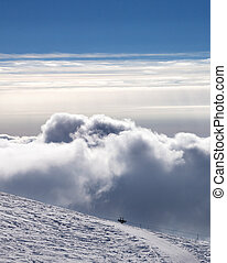 Snowy off-piste slope and beautiful sky with clouds at...