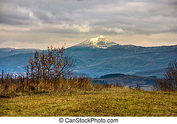 snowy peak over the meadow - high mountain snowy peak lit by...