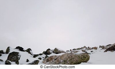 Snowy peaks of mountains. Autumn in mountains. Cloudy windy weather