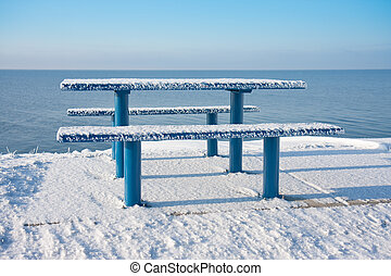 Snowy picnic table and bench along the dutch coast