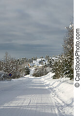 Snowy road leading to a village in a white winter landscape in western Norway.