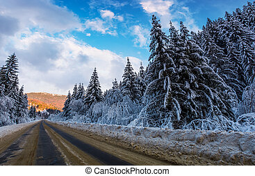 snowy road through mountains in evening. wonderful nature...