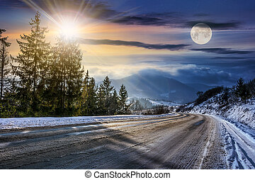 snowy road through spruce forest in mountains - day and...