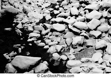 Snowy rocks in empty riverbed