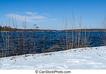 Snowy shore of Glienicke lake on Havel river