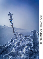 Snowy signpost on a mountain peak
