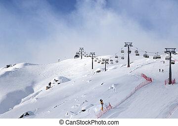 Snowy ski slope and ski-lift at ski resort at sunny winter...
