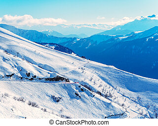 Snowy ski slopes in the background of mountain ranges and blue sky with clouds