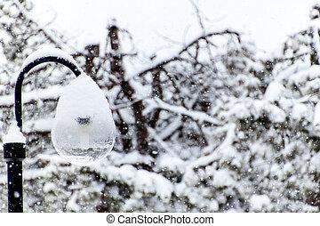 Snowy street lamp in snow blizzard. Modern ecological lighting. Winter mood.