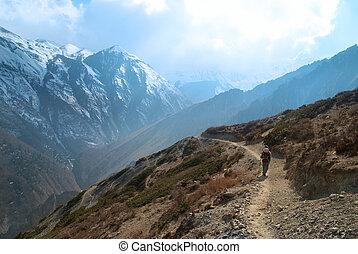 Snowy Tibetan mountains with hiking man