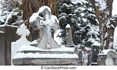 Snowy tombstone on the graveyard, with Jesus on cross, on wintertime.