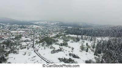 Snowy village in the valley of wooded hills. Aerial view