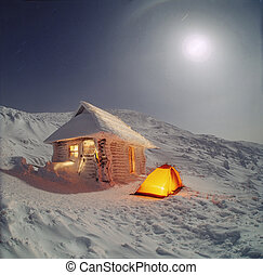 High in the mountains of the Carpathians are houses for tourists, who are blocked with snow in winter. They are very beautiful night and day